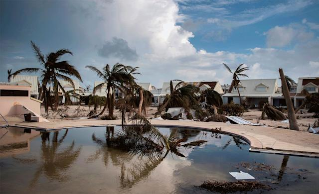 A pool surrounded by wrecked bungalows in Marigot on Sept. 10 and the same pool filled with sand on Feb. 28.