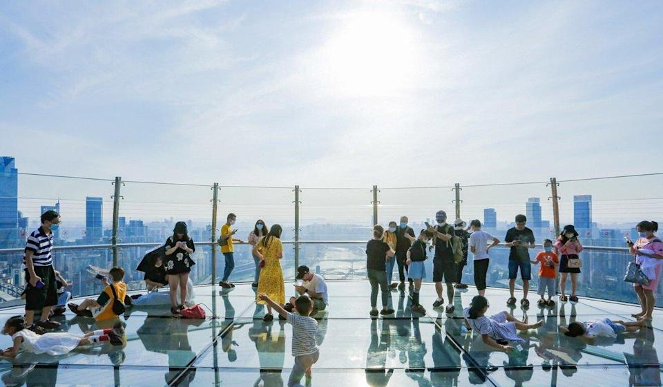 Visitors take in the views of Chongqing from the glass-bottomed sky deck at Raffles City Chongqing. The development is among the nine Raffles City projects CapitaLand has built in China. It is among the three properties in which Ping An has not acquired a stake. Photo: Handout