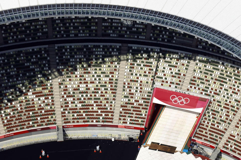 FILE - In this June 21, 2021, aerial file photo, the Olympic Rings are seen with spectators' seats at the National Stadium in Tokyo Japan. The Olympic corporate sponsorship program has been a key part of the Olympic experience since it began in 1985. But all that magic from the Olympic sponsorship is being undermined because of the virus. .(Kyodo News via AP)