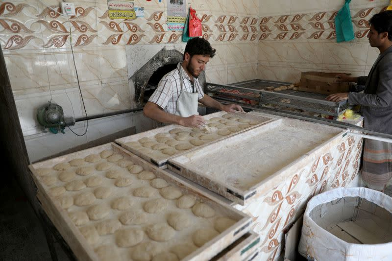 A man prepares bread dough before baking it in a wood-fired oven due to fuel shortages in Sanaa
