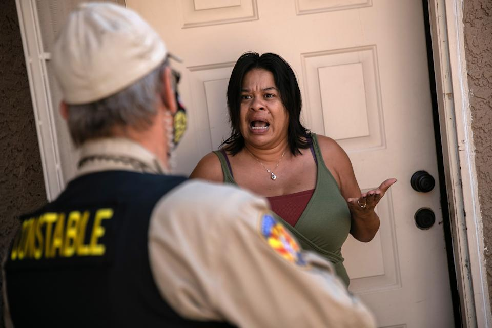 PHOENIX, ARIZONA - OCTOBER 07: A tenant speaks with a Maricopa County constable who arrived with an eviction order on October 7, 2020 in Phoenix, Arizona. The tenant was able to prove she had paid the rent and the order was withdrawn. Thousands of court-ordered evictions continue nationwide despite a Centers for Disease Control (CDC) moratorium for renters impacted by the coronavirus pandemic. Although state and county officials say they have tried to educate the public on the protections, many renters remain unaware and fail to complete the necessary forms to remain in their homes. In many cases landlords have worked out more flexible payment plans with vulnerable tenants, although these temporary solutions have become fraught as the pandemic drags on. With millions of Americans still unemployed due to the pandemic, federal rental assistance proposals remain gridlocked in Congress. The expiry of the CDC moratorium at year's end looms large, as renters and landlord face a potential tsunami of evictions and foreclosures nationwide.  (Photo by John Moore/Getty Images)