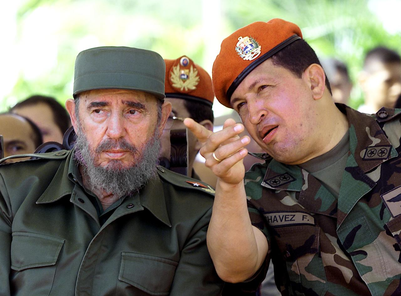 Cuban leader Fidel Castro  and Venezuelan Hugo Chavez talk in  Pampatar Bay near Caracas, Venezuela Tuesday Dec, 11, 2001 where they participate at a rally to dedicate a new economic project to help poor Venezuelan fishermen. Castro is in Venezuela to attend a Caribbean association summit. (AP Photo/Jose Goitia)