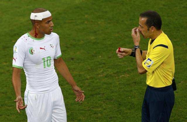 Referee Cuneyt Cakir of Turkey talks to injured Algeria's Sofiane Feghouli during the 2014 World Cup Group H soccer match between Algeria and Russia at the Baixada arena in Curitiba June 26, 2014. REUTERS/Amr Abdallah Dalsh (BRAZIL - Tags: SOCCER SPORT WORLD CUP)