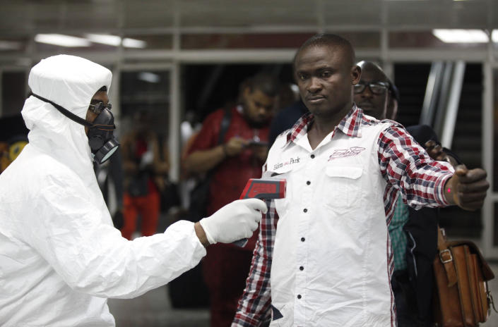 A Nigerian port health official uses a thermometer on a worker at Muhammed International Airport. (Sunday Alamba/AP)