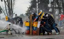 Demonstrators stand behind makeshift shields during clashes with riot police in the city of Madrid, Colombia