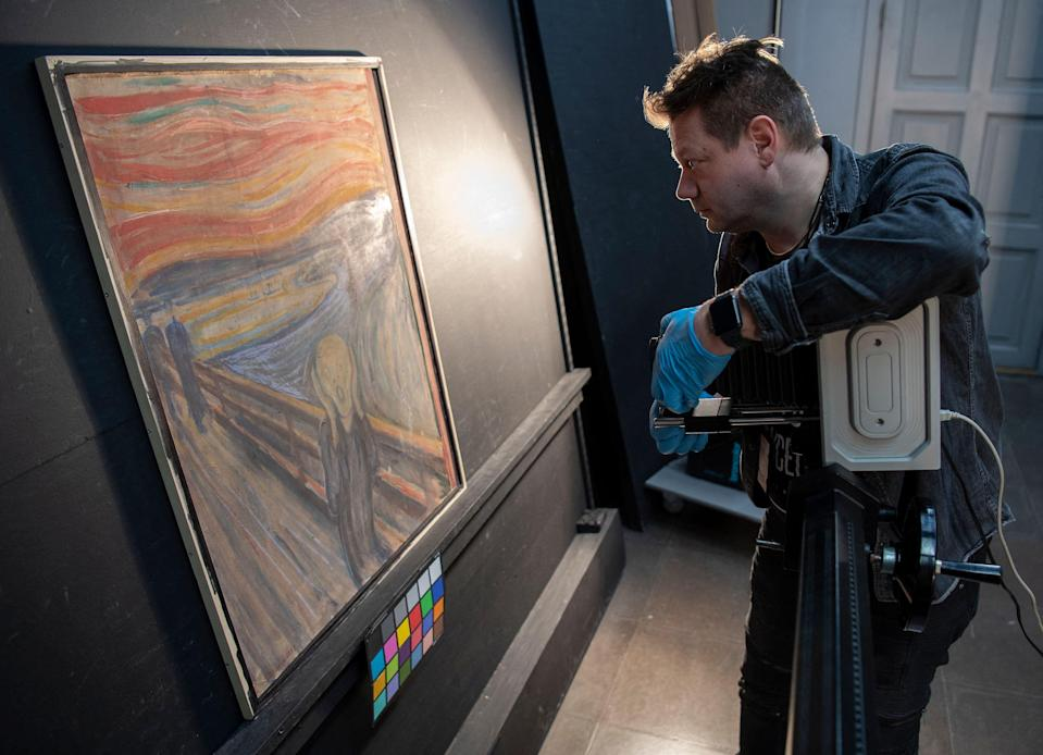 """A curator at the National Museum of Norway uses an infrared scanner to reveal author of a scribbled sentence on Edvard Munch's 1893 painting """"The Scream"""" in Oslo."""