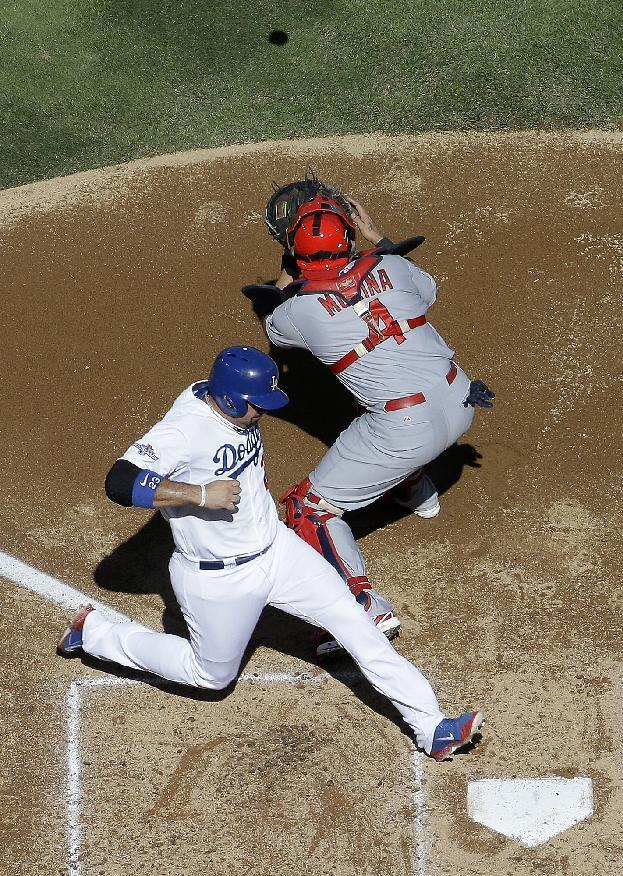Los Angeles Dodgers' Adrian Gonzalez scores from second past St. Louis Cardinals catcher Yadier Molina on a hit by Juan Uribe during the second inning of Game 5 of the National League baseball championship series Wednesday, Oct. 16, 2013, in Los Angeles. (AP Photo/Morry Gash)