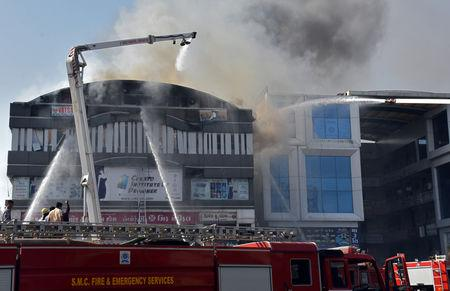 Firefighters douse a fire that broke out in a four-story commercial building in Surat, in the western state of Gujarat, India, May 24, 2019. REUTERS/Stringer NO ARCHIVES. NO RESALES.