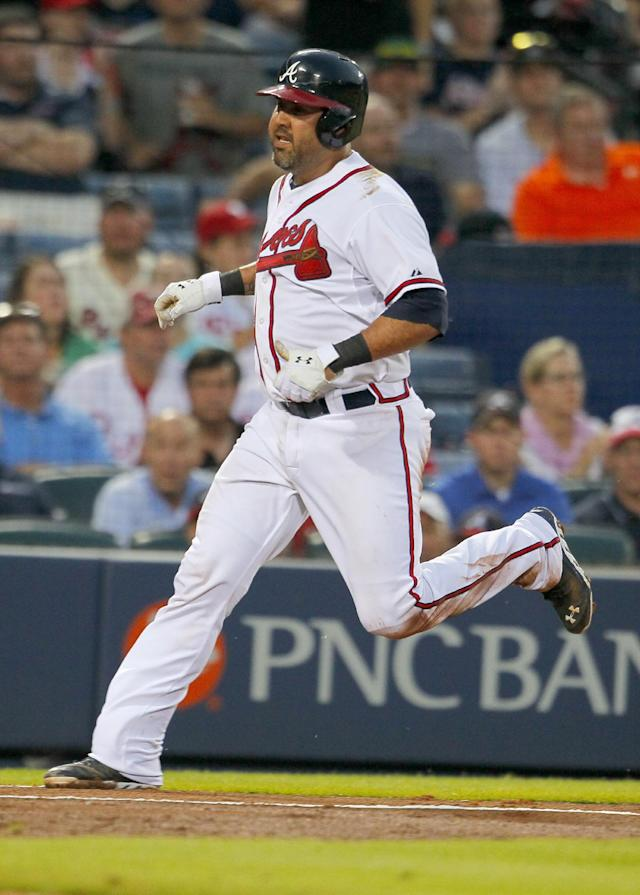 Atlanta Braves Gerald Laird (11) scores from a double hit by Jason Heyward (22) in the fifth inning of a baseball game against the Philadelphia Phillies Tuesday, June 17, 2014, in Atlanta. (AP Photo/Todd Kirkland)