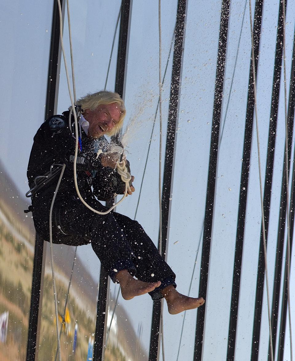 Sir Richard Branson sprays champagne after repelling down the side of the new Spaceport America hangar.