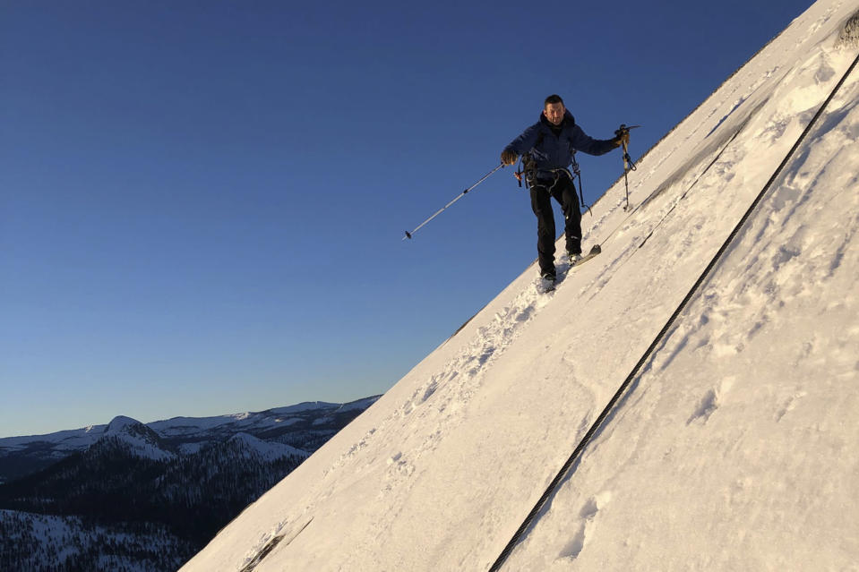 """In this photo provided by Jason Torlano, Zach Milligan is shown on his descent down Half Dome in Yosemite National Park, Calif., on Sunday, Feb. 21, 2021. Two men climbed some 4,000 feet to the top of Yosemite's Half Dome in subfreezing temperatures and skied down the famously steep monolith to the valley floor. Jason Torlano, 45, and Zach Milligan, 40, completed the daring descent in five hours on Sunday by charging down Half Dome's arching back and using ropes to rappel down several sections of bare rock known as the """"death slabs,"""" the Fresno Bee reported on Thursday. (Jason Torlano via AP)"""