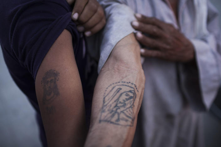 Coptic Christian men show their religious tattoos at Al-Mahraq monastery in Assiut, Upper Egypt, Tuesday, Aug. 6, 2013. Islamists may be on the defensive in Cairo, but in Egypt's deep south they still have much sway and audacity: over the past week, they have stepped up a hate campaign against the area's Christians. Blaming the broader Coptic community for the July 3 coup that removed Islamist President Mohammed Morsi, Islamists have marked Christian homes, stores and churches with crosses and threatening graffiti. (AP Photo/Manu Brabo)