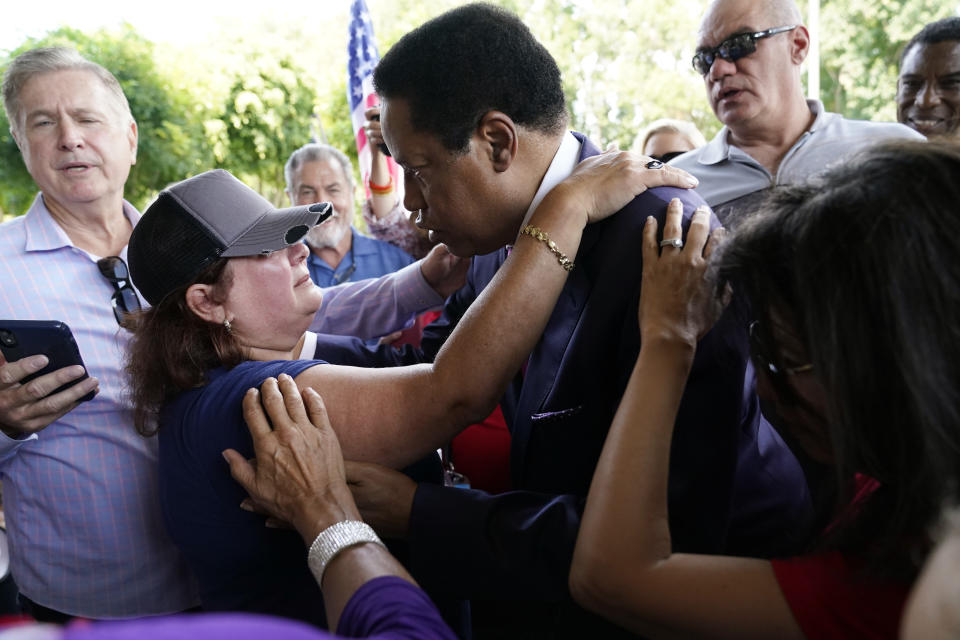 FILE — On this July 13, 2021 file photo conservative radio talk show host Larry Elder center right, is hugged by supporter Paulette Melton during a campaign stop, Tuesday, in Norwalk, Calif. Elder, who is running to replace Democratic Gov. Gavin Newsom in the Sept. 14 recall election, says he would erase state vaccine and mask mandates, is critical of gun control, opposes the minimum wage and disputes the notion of systemic racism in America. (AP Photo/Marcio Jose Sanchez, File)