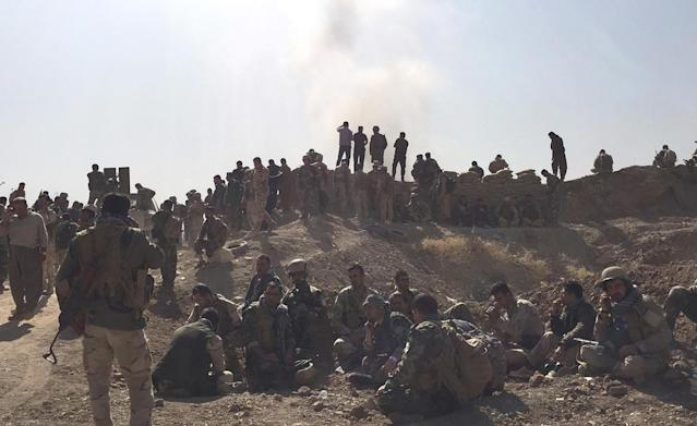 Peshmerga soldiers wait and watch behind a fortified position while exlosion goes off down the road. (Photo: Ash Gallagher for Yahoo News)