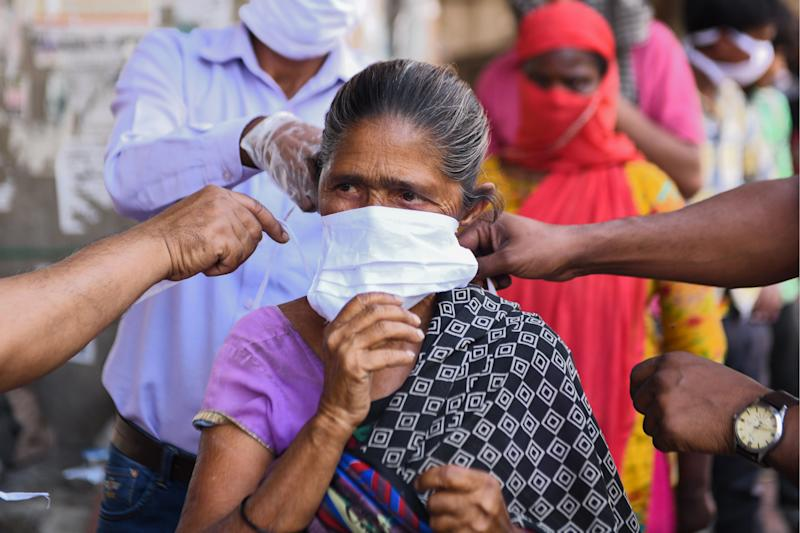 Volunteers of the Diocese of Amritsar Church of North India distribute facemasks to people during a government-imposed nationwide lockdown as a preventive measure against the COVID-19 coronavirus, in Amritsar on April 15, 2020. (Photo by NARINDER NANU / AFP) (Photo by NARINDER NANU/AFP via Getty Images)