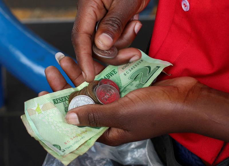 A petrol attendant counts local bonds notes and coins received from a motorist in Harare