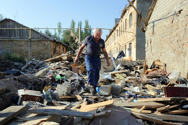 A man examines his destroyed house in Golmovsky village, Donetsk region, in August 2015 (AFP Photo/Aleksey Filippov)