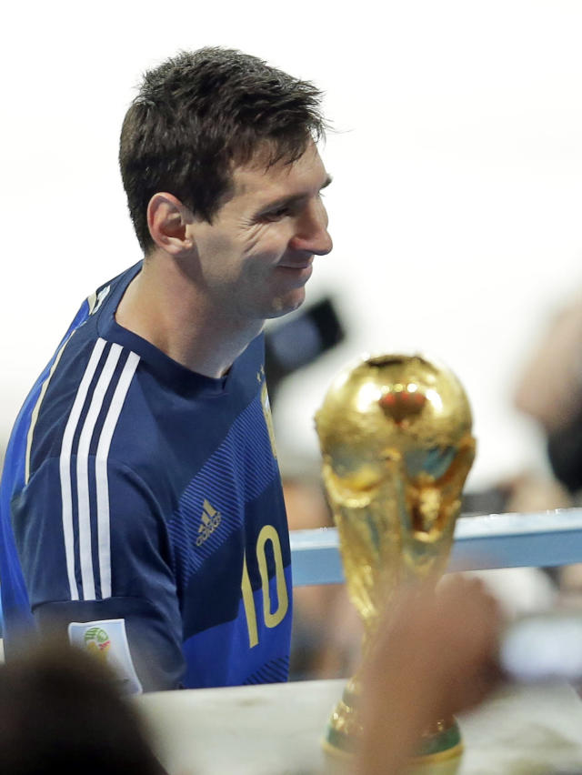 Argentina's Lionel Messi walks by the World Cup trophy as he goes on the tribune to collect the second place trophy after the World Cup final soccer match between Germany and Argentina at the Maracana Stadium in Rio de Janeiro, Brazil, Sunday, July 13, 2014. Germany won 1-0.(AP Photo/Hassan Ammar)