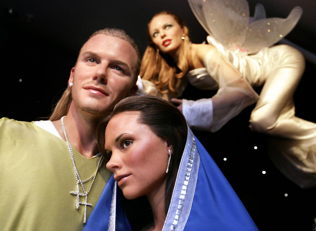 Wax works of England soccer captain David Beckham (L) and his wife Victoria appear as Joseph and Mary, with Australian singer Kylie Minogue (top R) as the angel in a new celebrity nativity scene at Madame Tussauds London, December 7, 2004. [The scene also features wax works of U.S. actor Samuel L. Jackson, British actor Hugh Grant and Irish comedian Graham Norton as the shepherds and Britain's Prime Minister Tony Blair, the Duke of Edinburgh and U.S. President George W. Bush as the three wise men.] Peter MacDiarmid / Reuters