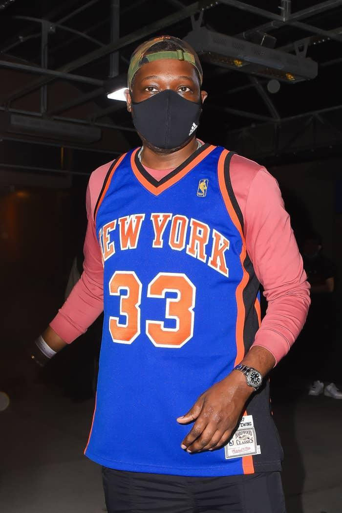 Michael Che walking outdoors in a New York Knicks jersey over a long-sleeved shirt, a bucket hat, and a face mask