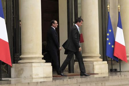 French President FrancoisHollande (L) watches as Prime Minister Manuel Valls leaves after their meeting at the Elysee Palace in Paris, August 25, 2014. REUTERS/John Schults