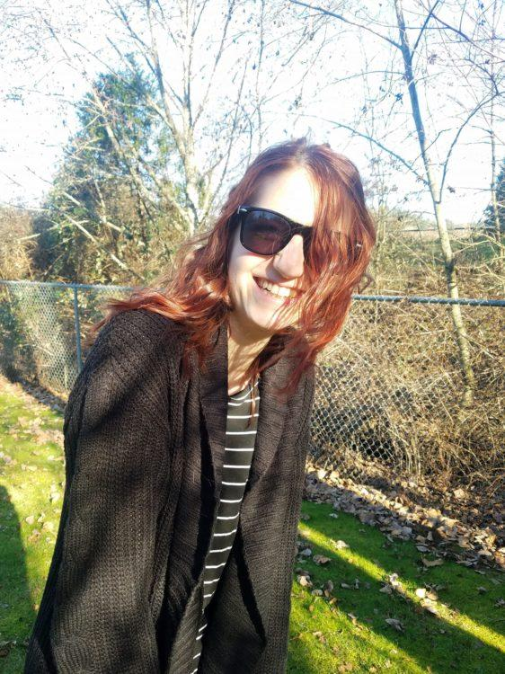 A photo of a young woman smiling into the camera, wearing sunglasses.