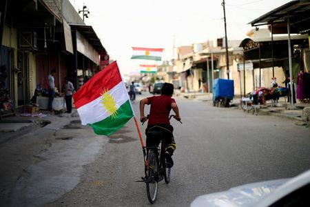A boy rides a bicycle with the flag of Kurdistan in Tuz Khurmato