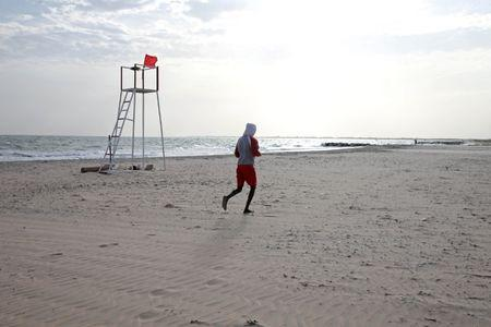 A man jogs on the beach in Bakau