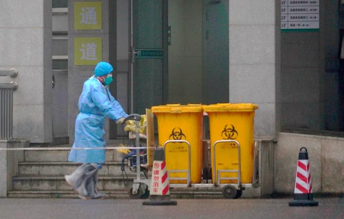 Staff move bio-waste containers past the entrance of the Wuhan Medical Treatment Center, where some infected with a new virus are being treated, in Wuhan, China, Wednesday, Jan. 22, 2020.