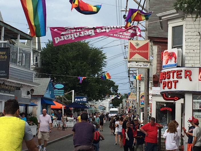 provincetown street with people, flags, crowds