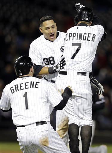 Chicago White Sox's Jeff Keppinger (7) celebrates with Hector Gimenez (38) and Tyler Greene (1) after hitting the game-winning single against the Miami Marlins during the 11th inning of an interleague baseball game, Friday, May 24, 2013, in Chicago. The White Sox won 4-3. (AP Photo/Nam Y. Huh)