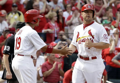 St. Louis Cardinals' Jon Jay, left, and Matt Holliday celebrate after scoring on a fielding error Cincinnati Reds center fielder Shin-Soo Choo during the first inning of a baseball game Monday, April 8, 2013, in St. Louis. (AP Photo/Jeff Roberson)