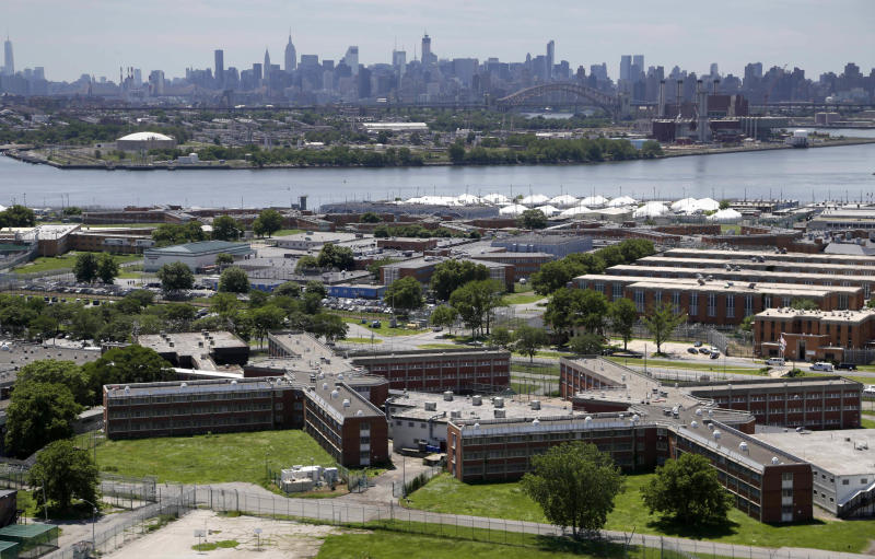 FILE - This June 20, 2014 file photo shows the Rikers Island jail complex in New York with the Manhattan skyline in the background. Health experts say prisons and jails are considered a potential epicenter for America's coronavirus pandemic. (AP Photo/Seth Wenig, File)