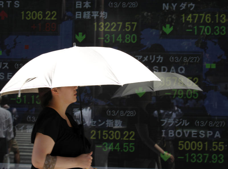 A woman walks past the day's Nikkei 225 stock index seen on a board in Tokyo, Japan, Wednesday, Aug. 28, 2013. The growing likelihood of Western military action against Syria pummeled Asian stock markets Wednesday and sent the price of oil soaring. (AP Photo/Shuji Kajiyama)
