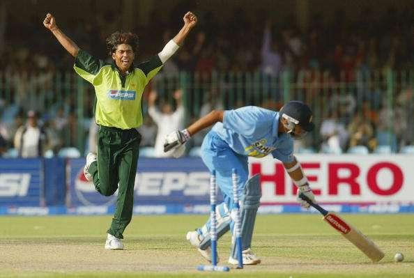 LAHORE, PAKISTAN - MARCH 24: Mohammad Sami (L) of Pakistan celebrates after dismissing Rahul Dravid of India during the fifth Pakistan v India one-day international match played at the Gadaffi Stadium on March 24, 2004 in Lahore, Pakistan. (Photo by Scott Barbour/Getty Images)