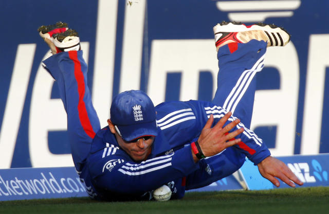 England's Steven Finn slides on the ground to prevent New Zealand from scoring a boundary during their T20 international cricket match at Seddon Park in Hamilton February 12, 2013. REUTERS/Simon Watts (NEW ZEALAND - Tags: SPORT CRICKET TPX IMAGES OF THE DAY) - RTR3DO66