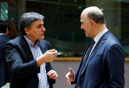 Greek Finance Minister Tsakalotos talks to European Commissioner Moscovici during a eurozone finance ministers meeting in Brussels