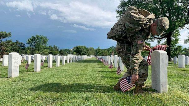 PHOTO: A soldier from the U.S. Army's 'Old Guard,' the 3rd U.S. Infantry Regiment, places American flags in front of more than 228,000 headstones in Arlington National Cemetery, May 23, 2019. (Jacqueline Yoo/ABC News)