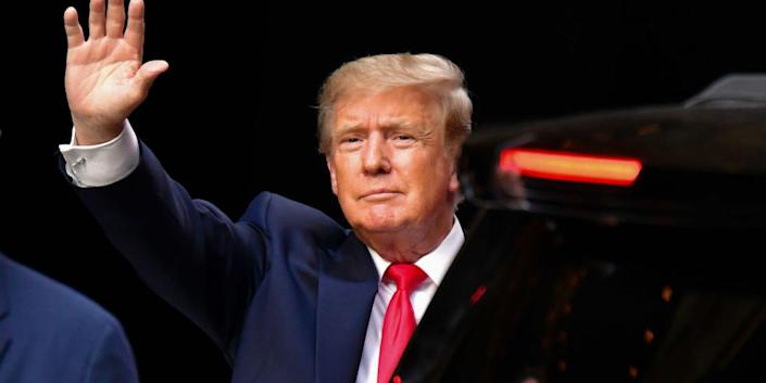 Donald Trump holding his right hand up to wave in front of a black background.