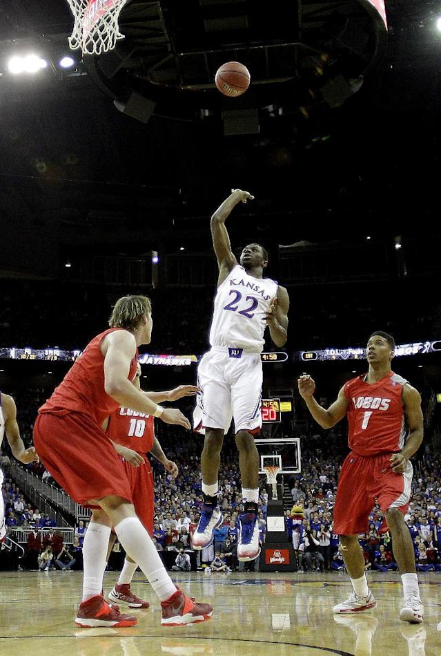 Kansas' Andrew Wiggins (22) puts up a shot between New Mexico's Cleveland Thomas (1) and Cameron Bairstow, left, during the first half of an NCAA college basketball game Saturday, Dec. 14, 2013, in Kansas City, Mo. (AP Photo/Charlie Riedel)