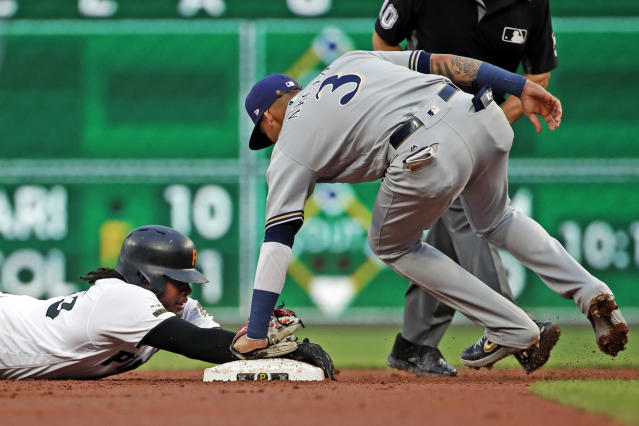 Milwaukee Brewers shortstop Orlando Arcia (3) holds the tag on Pittsburgh Pirates' Josh Bell as he slides safely around second with a double off starting pitcher Chase Anderson during the second inning of a baseball game in Pittsburgh, Thursday, May 30, 2019. (AP Photo/Gene J. Puskar)