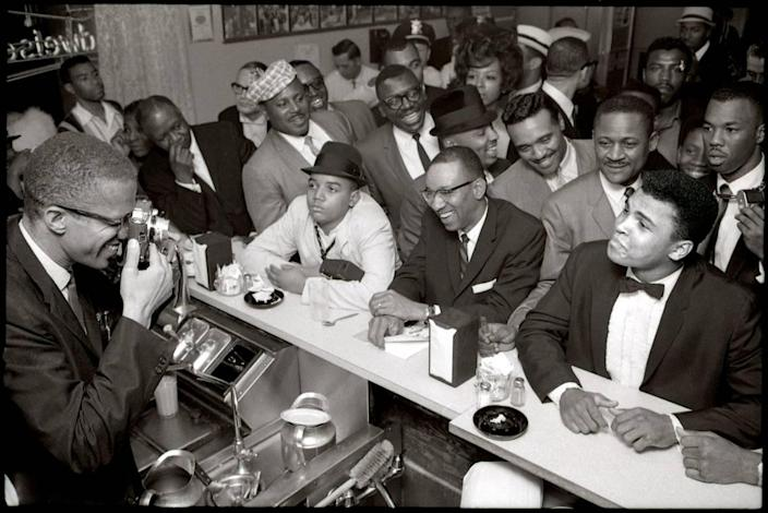 Malcolm X trains his camera on the tux-clad Cassius Clay, smugly sitting at the counter of Miami's Hampton House in 1964, surrounded by jubilant fans after he beat Sonny Liston for the heavyweight championship of the world title on Feb. 25, 1964, in Miami Beach. The next day, Clay announced he had become a member of the Nation of Islam. Many prominent black leaders, sports figures and entertainers stayed at The Hampton House in Brownsville near Liberty City, including the Rev. Martin Luther King Jr.