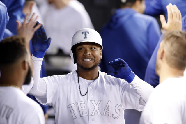 Texas Rangers' Willie Calhoun celebrates in the dugout with teammates after hitting a two-run home run during the sixth inning of a baseball game against the Chicago White Sox, Saturday, Aug. 24, 2019, in Chicago. (AP Photo/Jeff Haynes)