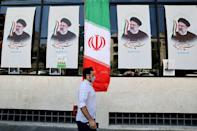 An Iranian man walks by posters of presidential candidate Ebrahim Raisi outside a campaign office in Tehran on June 7