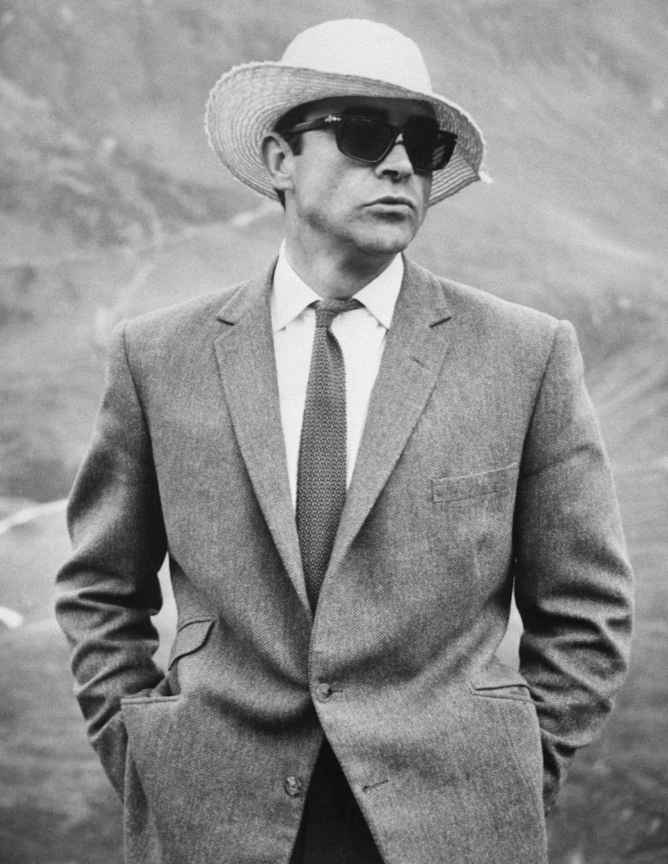 <p>Sean Connery relaxing between scenes on the 'Goldfinger', 1964 set wearing sunglasses and sun hat. </p>