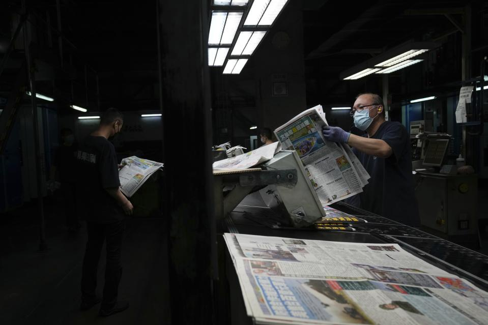Workers check the copies of Apple Daily newspaper at the printing house in Hong Kong, early Friday, June 18, 2021. Five editors and executives at pro-democracy Apple Daily newspaper were arrested Thursday under Hong Kong's national security law, its stock was halted and police were searching its offices in moves raising concerns about the media's future in the city. (AP Photo/Kin Cheung)