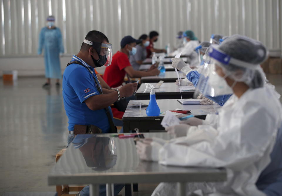 Thai residents and Myanmar migrant workers register for a Covid-19 nasal swab test as an effort to stop the spread of the outbreak cluster at Bang Yai market. Source: AAP