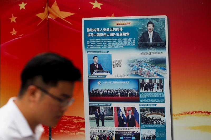 "A man walks by a government propaganda billboard promoting Chinese President Xi Jinping's signature ""One Belt One Road"" outside a subway station in Beijing, Tuesday, Aug. 28, 2018. Chinese officials on Monday defended Beijing's initiative to build a ""New Silk Road"" of railways and other infrastructure across Asia against complaints it leaves host countries with too much debt after Malaysia canceled two high-profile projects. The officials said President Xi Jinping's signature foreign policy initiative is creating assets that are needed by developing countries but might take time to pay off. (AP Photo/Andy Wong)"