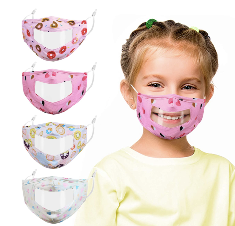 blonde little girl smiling wearing a clear and pink face mask for back to school