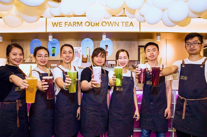 Seven staff members at the Gotcha Fresh Tea restaurant in Melbourne are standing in a line holding different kinds of fresh tea.